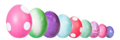 Färgrika färgade easter ägg i en linje, högväxt format till det lilla formatet som isoleras på vit arkivfoton