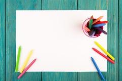 färgrika färgpennor och tomt papper på skrivbordet Arkivbild