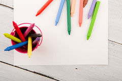 färgrika färgpennor och tomt papper på skrivbordet Fotografering för Bildbyråer