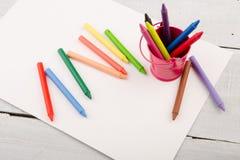färgrika färgpennor och tomt papper på skrivbordet Arkivfoton
