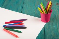 färgrika färgpennor och tomt papper på skrivbordet Arkivbilder