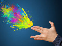 Färgrika färgstänk är kommande ut ur vapnet formade händer Arkivbild