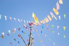 Färgrika flaggor av buddismceremoni på den thailändska templet Fotografering för Bildbyråer