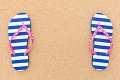 Färgrika flipfloppar på strandsanden royaltyfri foto