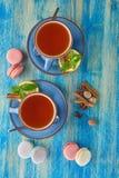 Färgrika franska makron och två kopp te Arkivbilder