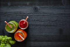Färgrika fruktsafter för fruktsaftstång tre med sugrör på mörk träyttersida Arkivfoton