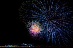 Färgrika fyrverkerier för natt i himlen över staden i Europa royaltyfri fotografi