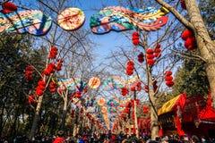 Färgrika garneringar och röda lyktor på mässa för tempel för vårfestival, under kinesiskt nytt år royaltyfria foton