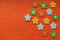 Färgrika garneringar på ljus orange bakgrund Arkivfoton