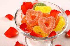 Färgrika gelégodisar i hjärtaform med blommasidor Royaltyfria Foton