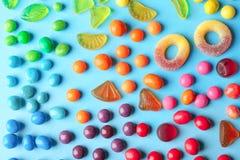 Färgrika godisar på bakgrund Arkivfoton