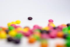 Färgrika godisar, på vit bakgrund Arkivbild