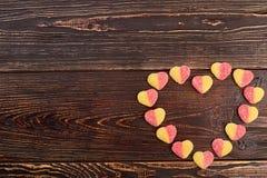 Färgrika godisar som bildar hjärtaform royaltyfria bilder