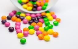 Färgrika godisar som isoleras på vit bakgrund Arkivfoton