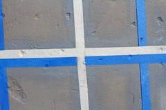 Färgrika grå färger, blått och vit målade väggen med sprickor royaltyfria foton