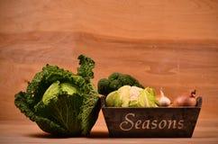 Färgrika grönsaker kål, blomkål, broccoli, potatis, lök på trätabellen Arkivfoto