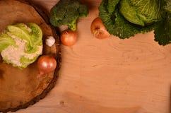 Färgrika grönsaker kål, blomkål, broccoli, potatis, lök på trätabellen Top beskådar Fritt avstånd för text Arkivfoto