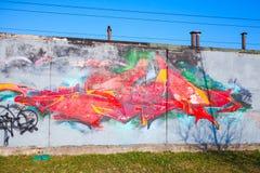 Färgrika grafitti med den kaotiska röda modellen över gammal grå concret Arkivfoton