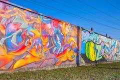 Färgrika grafitti med draken och kaotiska modeller över gammal gra Royaltyfri Bild