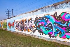 Färgrika grafitti med kaotiska modeller över gamla grå färger hårdnar G Arkivfoton