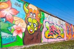 Färgrika grafitti med tecknad filmteckenet över gamla grå färger hårdnar Fotografering för Bildbyråer