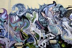 Färgrika grafitti på den texturerade tegelstenväggen Royaltyfri Fotografi