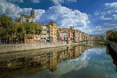 Färgrika guling- och apelsinhus och bron Pont de Sant Agusti reflekterade i vattenfloden Onyar, i Girona, Catalonia, Spanien Arkivbild