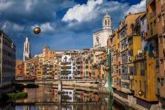 Färgrika guling- och apelsinhus och bron Pont de Sant Agusti reflekterade i vattenfloden Onyar, i Girona, Catalonia, Spanien Royaltyfri Fotografi