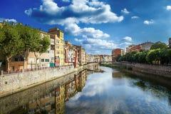 Färgrika guling- och apelsinhus och bron Pont de Sant Agusti reflekterade i vattenfloden Onyar, i Girona, Catalonia, Spanien Royaltyfria Foton