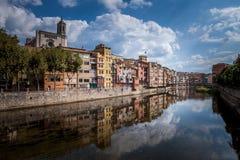 Färgrika guling- och apelsinhus och bron Pont de Sant Agusti reflekterade i vattenfloden Onyar, i Girona, Catalonia, Spanien Royaltyfri Bild