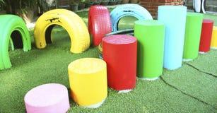 Färgrika gummihjulstolar och cylinderstolar på lekplatsen royaltyfri foto