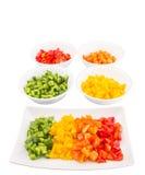 Färgrika högg av paprikor i bunke- och plattadropp Arkivbild