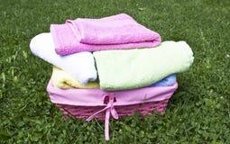 Färgrika handdukar i en vide- korg Arkivfoton