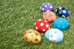 Färgrika handgjorda easter ägg på grönt gräs Arkivbild