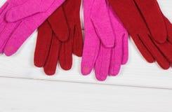 Färgrika handskar för kvinna på vita bräden och att bekläda för höst eller vinter Royaltyfri Bild