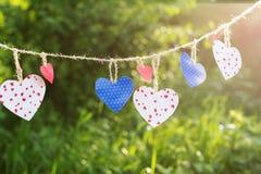 Färgrika hjärtor som hänger på grön bakgrund Fotografering för Bildbyråer