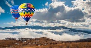 Färgrika hot-air ballonger som flyger över berg Konstnärlig pict Royaltyfri Bild