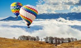 Färgrika hot-air ballonger som flyger över berg Konstnärlig pict Royaltyfri Foto