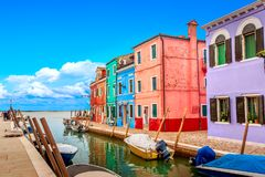 Färgrika hus i Burano nära Venedig, Italien med fartyg och härlig blå himmel i sommar Berömd turist- dragning i Venedig arkivfoto
