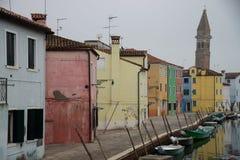Färgrika hus i den Burano ön nära Venedig, Italien på vattenkanalen med fartyg royaltyfri fotografi