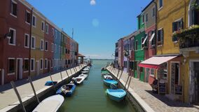 Färgrika hus och fartyg förtöjde längs kanalen på den Burano ön, lokaler i gata stock video