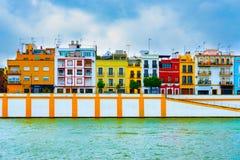Färgrika hus under en blå himmel vid den Guadalquivir floden arkivfoto