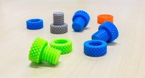 Färgrika idérika plast- skruvmuttrar kasta i sig och cirklar som göras av skrivaren 3D på trätabellen Royaltyfria Bilder