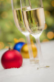 Färgrika julprydnader och Champagne Glasses på snö Arkivfoto
