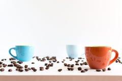 Färgrika kaffekoppar på den vita tabellen Royaltyfria Foton