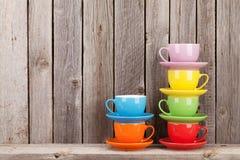 Färgrika kaffekoppar på hylla arkivbild