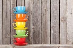 Färgrika kaffekoppar på hylla Arkivfoto