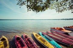 Färgrika kajaker förtöjde på lakeshore, Goldopiwo sjön, Mazury, Pol Royaltyfri Bild