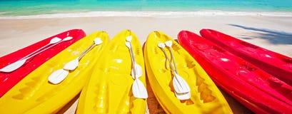 Färgrika kajaker med skovlar på en tropisk strand i solig sommar, ljusa vågor och turkoshavsvattenbakgrunder semestrar royaltyfria foton