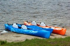 Färgrika kajaker och kanoter på den sandiga stranden fotografering för bildbyråer